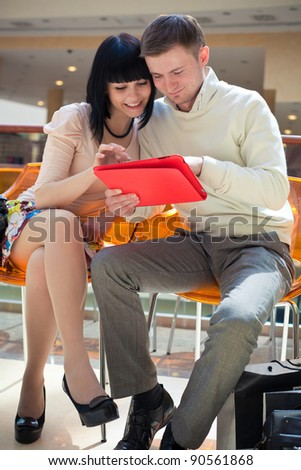 Couple shopping on internet with touch screen tablet computer