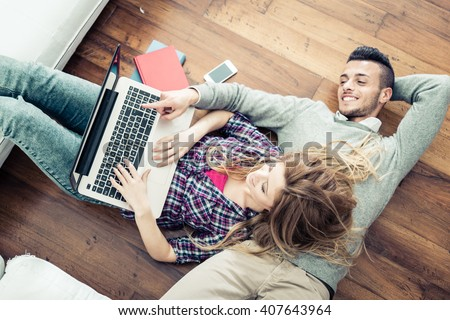 Couple shopping online at laptop computer - Two young friends watching a video on a notebook in the living room, view from above