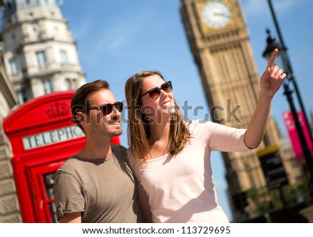 Couple sightseeing in London pointing away near the Big Ben