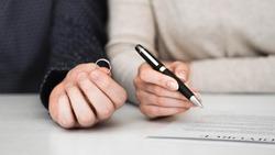 Couple signing divorce divorce settlement agreement. Separation contract document.