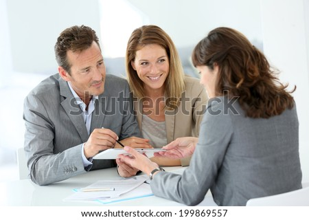 Couple signing loan grant on digital tablet