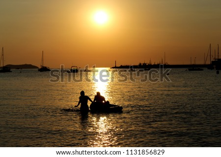 Couple silhouette at sunset in the water of San Antonio Bay, Ibiza.  #1131856829