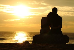 Couple silhouette cuddling and watching sun at sunset on the beach