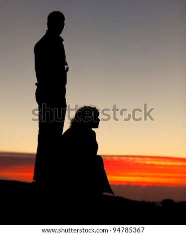 Couple silhouette on the beach at sunset.