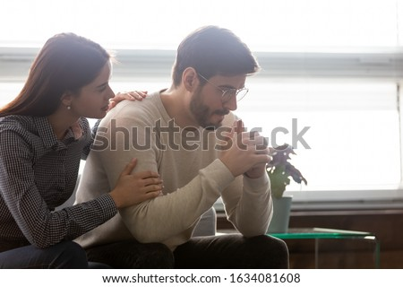Couple sit on sofa caring wife hugs disappointed sad frustrated husband, making peace, reconcile after fight, problems in relationship, friendship and support spouses overcome problem together concept