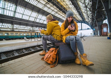 couple sit on valise at railway station. surfing internet while wait for train. travel concept