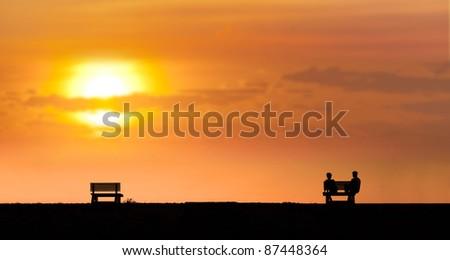 couple sit under sunset