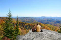 Couple siting on top of mountain rock. Blue sky in background. Father with arms around his daughter looking at beautiful autumn landscape, on hiking trip. Blue Ridge Mountains, North Carolina, USA.