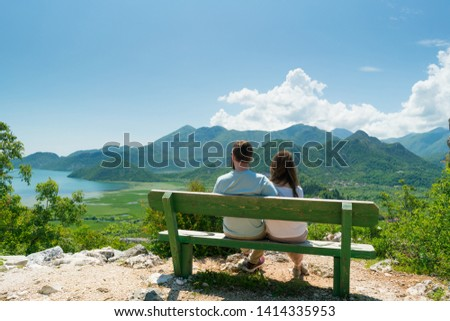couple sits on a bench and admires the view of the lake and hills #1414335953