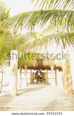 Couple sitting at a table underneath thatch roof