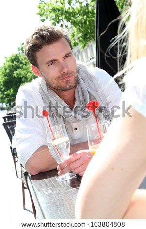 Couple sitting at an outdoor cafe to have a drink
