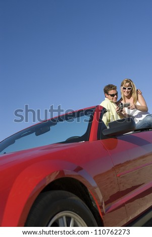 Couple sitting at backside of car watching a camcorder