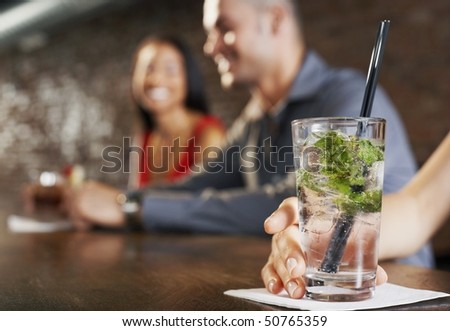 Couple sitting at bar, cocktail glass in foreground