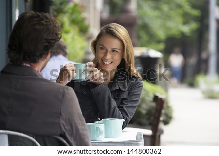 Couple sitting at sidewalk cafe