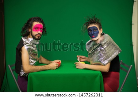 Couple sitting at the green table. Green background. Actors in the studio. Clowns. Futuristic makeup. Futuristic costumes. #1457262011