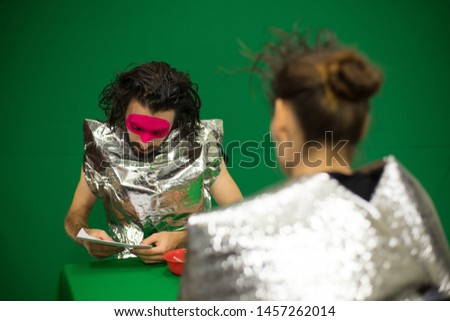 Couple sitting at the green table. Green background. Actors in the studio. Clowns. Futuristic makeup. Futuristic costumes. #1457262014