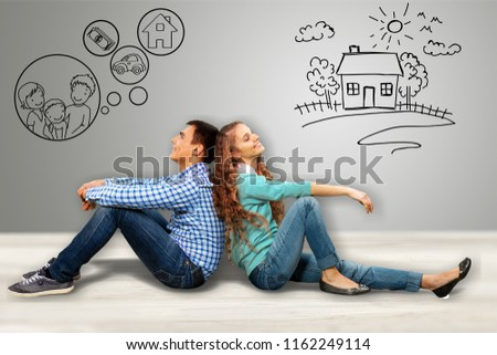 Couple sitting back-to-back dreaming with doodle pictures on wall #1162249114
