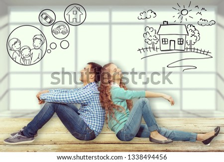 Couple sitting back-to-back dreaming with doodle pictures on wall #1338494456