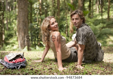 Couple sitting down in a tropical forest.