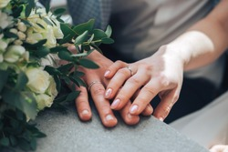 couple sitting holding hands with woman's hand on top of man's hand with wedding rings on close up