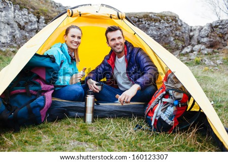 Couple sitting in a tent. Camping near the rocks