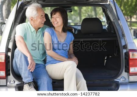 Couple sitting in back of van smiling