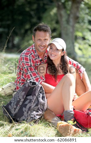 Couple sitting in nature on hiking day - stock photo
