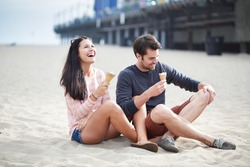 couple sitting in sand at santa monica pier.