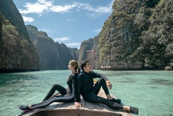 Couple sitting in the front of a longtail boat making a tour, sea in Pileh Lagoon Andaman sea, Phi Phi Islands, Thailand.