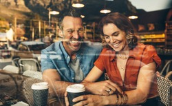 Couple sitting inside a cafe and smiling. Couple on a date at a local coffee shop.