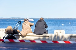 couple sitting on a bench with a pram