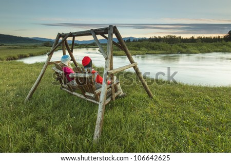 Couple sitting on a swing on a cold morning