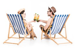 couple sitting on beach chairs and clinking with cocktail glasses, isolated on white
