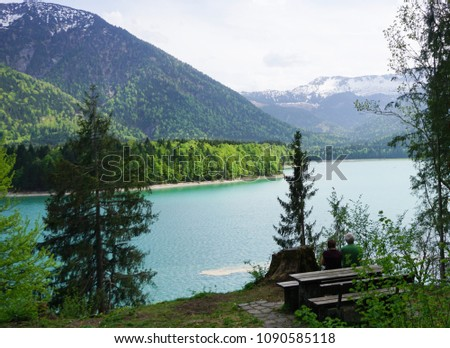 Couple sitting on bench and enjoying the view on a very blue lake in the mountains of Bavaria in Germany with forrest #1090585118