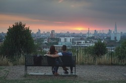 Couple sitting on bench enjoys the London skyline at sunset from a romantic spot near Greenwich park in summer