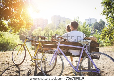 couple sitting on bench looking ...