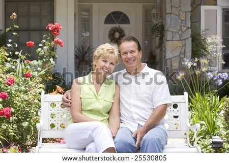 Couple Sitting On Bench Outside House