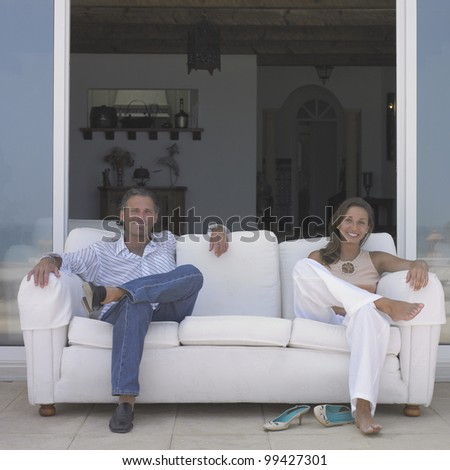 Couple sitting on couch - stock photo