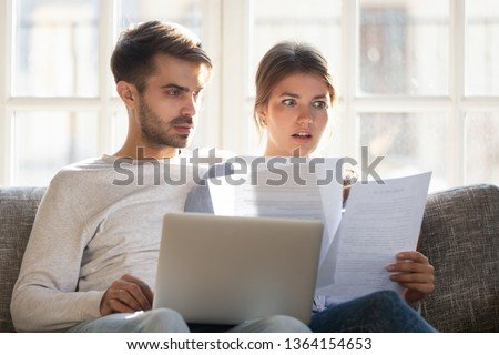 Couple sitting on couch at home use pc reading letter contract conditions terms feels stressed receive notice from bank account balance having due debt, check unpaid bills, financial problems concept