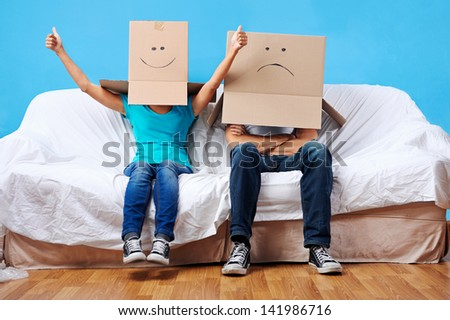 couple sitting on couch with moving boxes on head having fun together