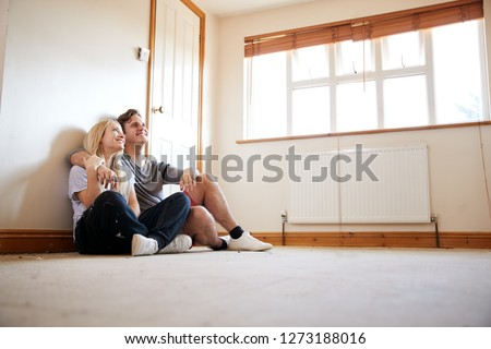 Couple Sitting On Floor In Empty Room Of New Home Planning Design
