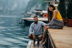Couple sitting on lake pier and sharing some relaxing moments.