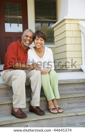 Couple sitting on outdoor steps of home smiling. Vertically framed shot.