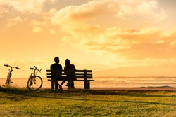 Couple sitting on park bench watching the sunset.