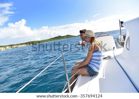 Couple sitting on sailboat deck looking at scenery #357694124