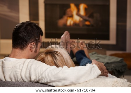 Couple sitting on sofa at home in front of fireplace, rear view. - stock photo