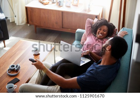 Couple Sitting On Sofa At Home Using Laptop Computer And Watching TV