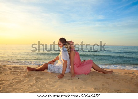 Couple sitting on the beach at sunrise time.