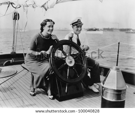 Couple sitting on the deck of a sailboat steering the boat