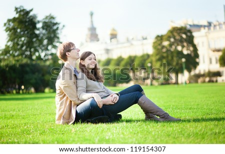 Couple sitting on the grass in Saint-Petersburg, Russia